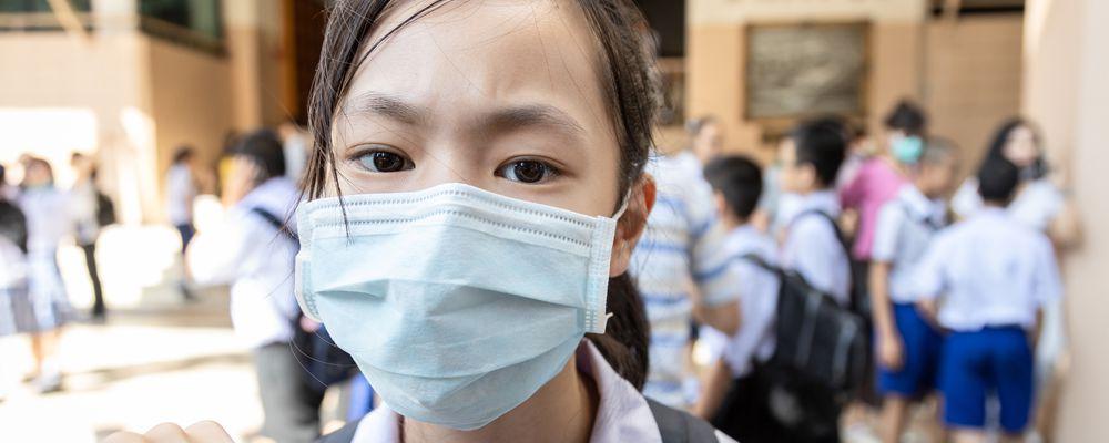 Asian girl student wearing medical face mask in school, epidemic, spread of germ, Coronavirus